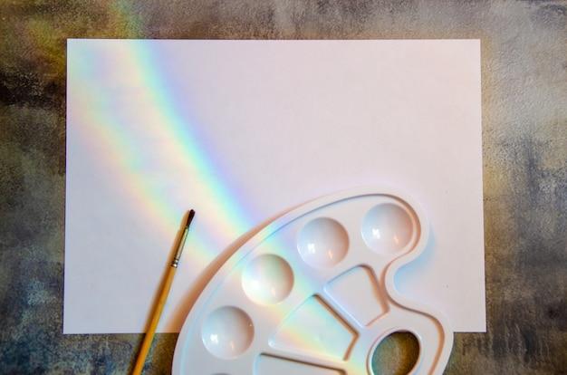 Foglio bianco di carta bianca con un arcobaleno, un pennello e una tavolozza bianca vuota per mescolare le vernici. materiali per artisti. trovare ispirazione