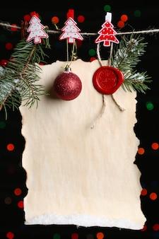 Foglio bianco con decorazioni natalizie su sfondo nero con luci