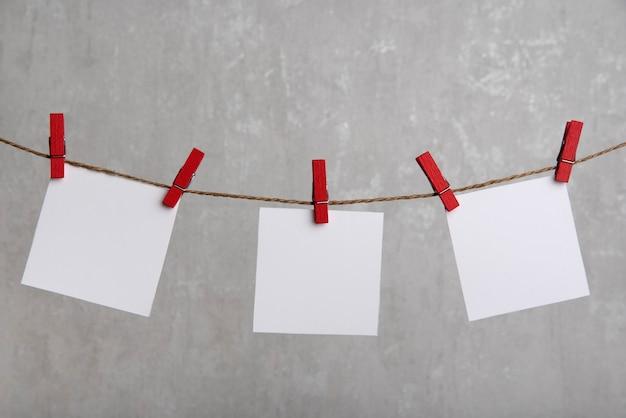 Fogli di carta bianchi appesi con mollette sulla corda. posto per il tuo testo. copia spazio.