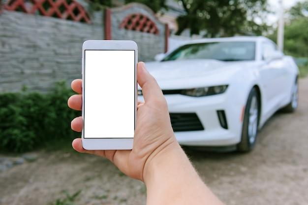 Smartphone in bianco in mano d'uomo, in macchina di sfondo bianco
