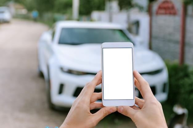 Smartphone in bianco nelle mani della donna, nell'auto di sfondo bianco