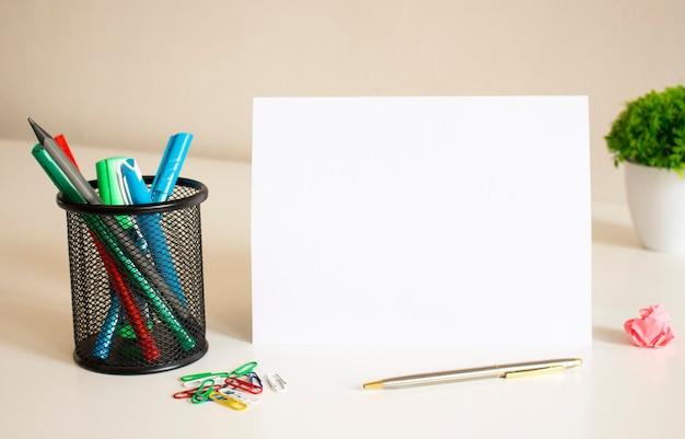 Spazio vuoto per l'iscrizione su un foglio di carta piegato bianco sul tavolo. nelle vicinanze ci sono penne e matite.