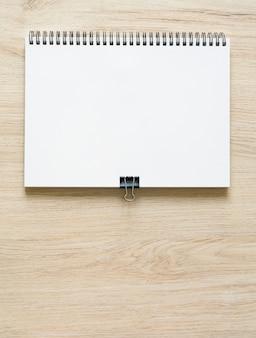 Modello di mockup di blocco note rilegato a spirale in bianco con copertina in carta kraft, isolato su sfondo di legno. alta risoluzione.