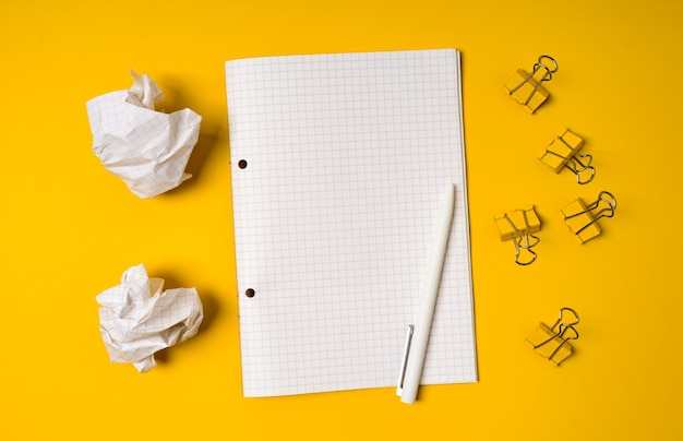 Taccuino a spirale in bianco e palline di carta sbriciolate su sfondo giallo