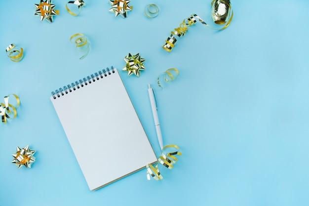 Blocco note a spirale in bianco con la penna bianca su un fondo blu con i coriandoli e gli archi dorati. colore e stile alla moda. disteso. copia spazio. idea di blogger.