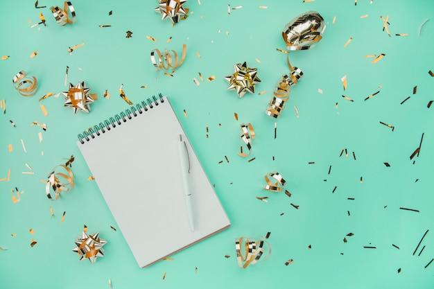 Blocco note a spirale in bianco con la penna bianca su un fondo verde con i coriandoli e gli archi dorati. colore e stile alla moda. l'appartamento stava mentendo. copia spazio. l'idea di un blogger.