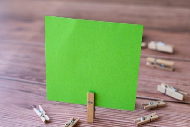 Nota quadrata vuota circondata da fermagli per bucato che mostrano un nuovo significato pezzo vuoto di carta adesiva