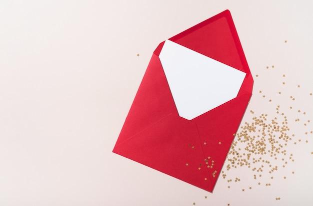 Busta di carta quadrata vuota mockup rossa, coriandoli di stelle dorate su sfondo beige