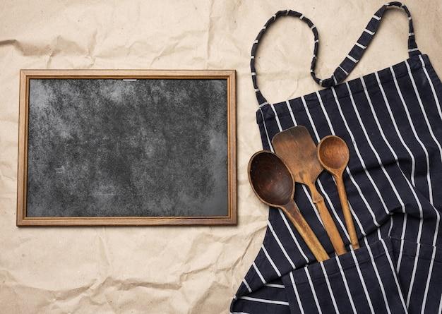 Cornice in legno quadrata vuota e grembiule da cuoco blu, vista dall'alto, copia dello spazio