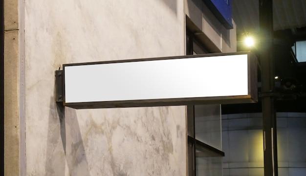 Mockup dell'insegna del negozio vuoto modello di lightbox del negozio illuminato vuoto montato sul muroxa