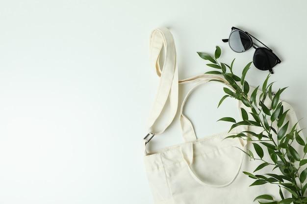 Borsa, ramo e occhiali da sole in bianco della tessile sulla superficie bianca