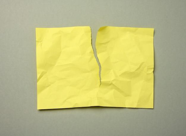 Foglio di carta giallo sgualcito strappato in bianco su uno sfondo grigio, copia dello spazio