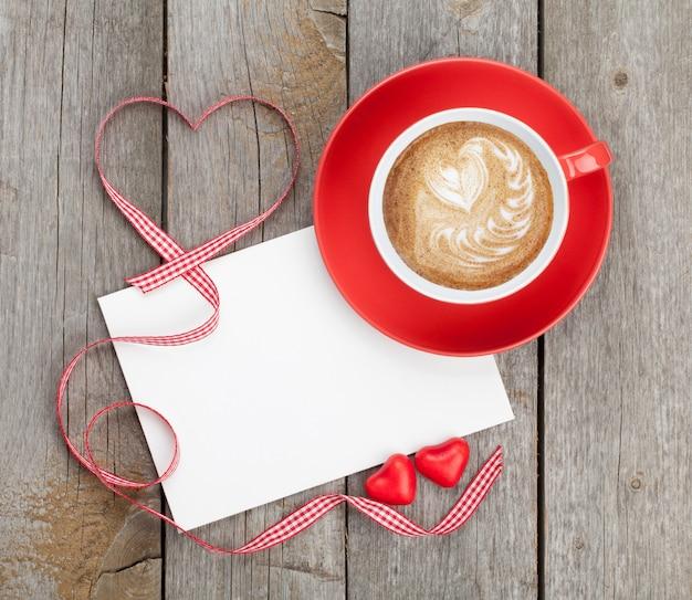 Biglietto di auguri di san valentino in bianco e tazza di caffè rossa su fondo in legno