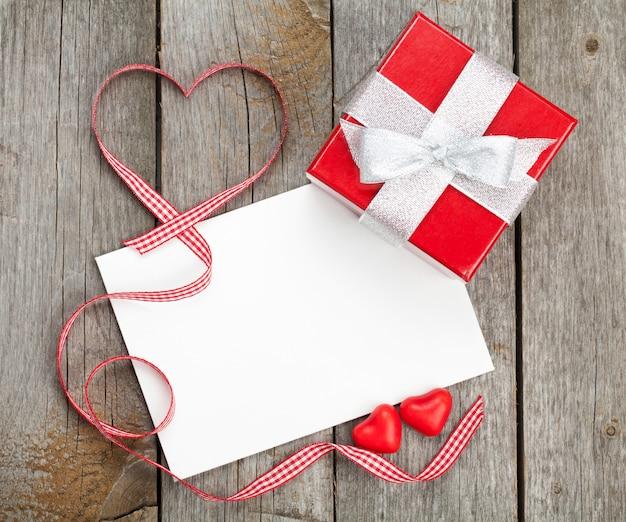 Biglietto di auguri di san valentino vuoto e piccola confezione regalo rossa su sfondo di legno