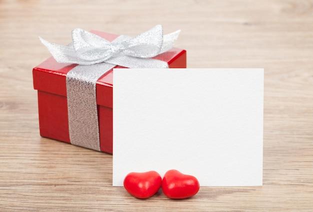 Biglietto di auguri di san valentino vuoto e piccola confezione regalo rossa sul tavolo di legno