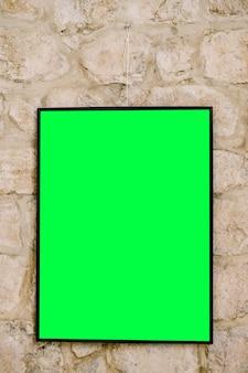 Pittura verticale vuota nella cornice nera sulla parete in muratura