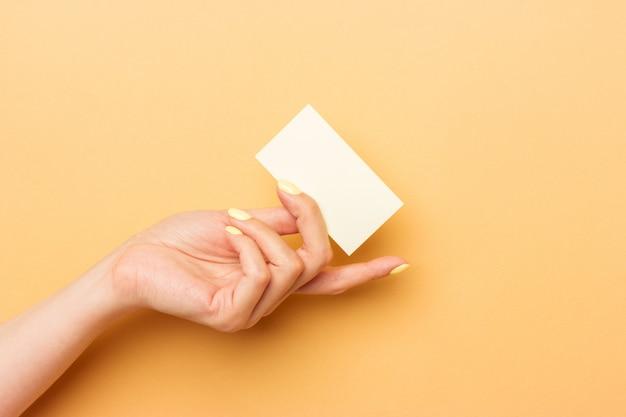 Biglietto da visita bianco in bianco che tiene in mano femminile