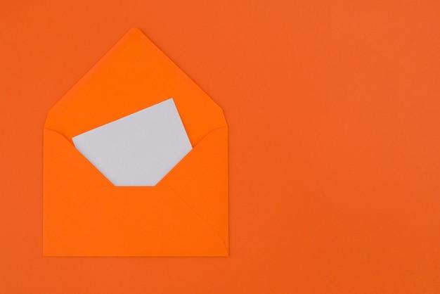 Scheda bianca vuota in busta arancione isolata su sfondo arancione pastello con spazio di copia.
