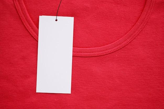 Etichetta bianca vuota dell'etichetta dei vestiti sulla nuova camicia rossa