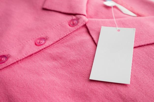 Etichetta bianca vuota dell'etichetta dei vestiti sulla nuova camicia