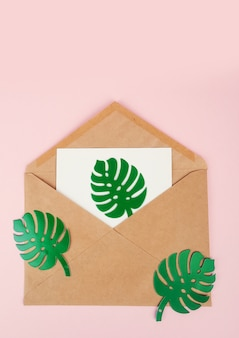Busta bianca vuota su foglio di carta monstera