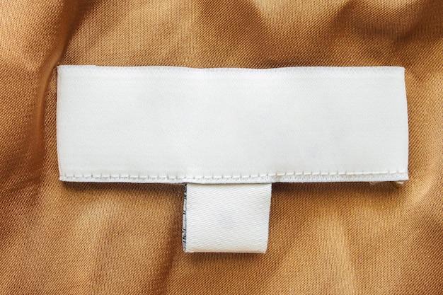 Etichetta bianca vuota dei vestiti per la cura del bucato sul fondo di struttura del tessuto marrone