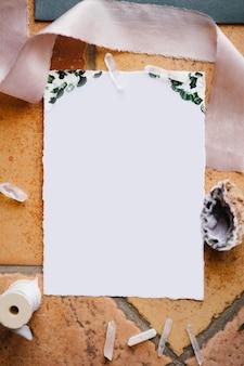 Una carta intestata bianca vuota giace su una piastrella di pietra incorniciata da un nastro, una conchiglia e una matassa di filo
