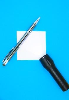 Adesivo bianco vuoto per la lista delle cose da fare con torcia e penna. ricerca di informazioni su internet. close up di promemoria carta su sfondo blu.