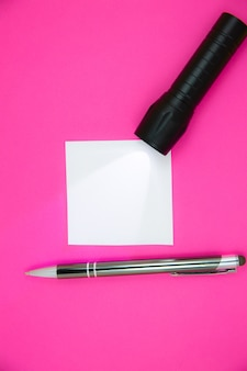 Adesivo bianco vuoto per la lista delle cose da fare con torcia e penna. ricerca di informazioni su internet. close up promemoria carta sullo sfondo rosa.