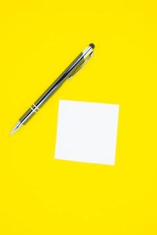Adesivo bianco vuoto per elenco attività con penna. ricerca di informazioni su internet. close up promemoria carta su sfondo giallo.