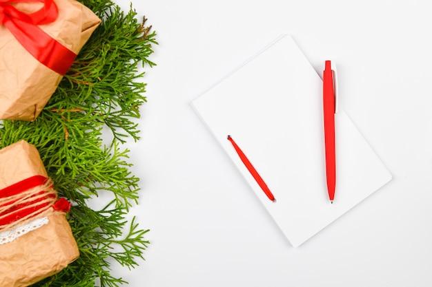 Taccuino bianco in bianco e penna rossa su priorità bassa bianca di natale
