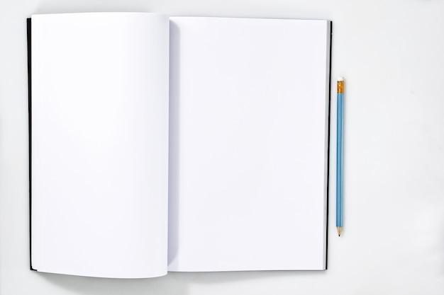Taccuino bianco in bianco sulla tavola di legno bianca con la matita sul taccuino. disegni mockup