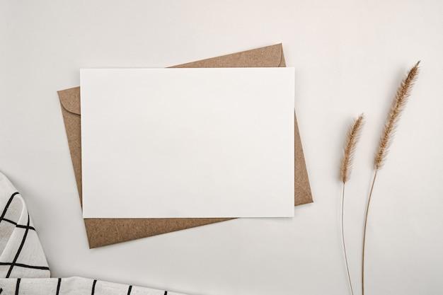 Carta bianca vuota su busta di carta marrone con fiore secco di coda di volpe ispida e griglia nera in tessuto bianco