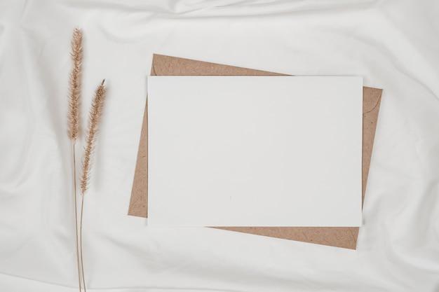 Libro bianco in bianco sulla busta di carta marrone con fiore secco di coda di volpe ispida sul panno bianco