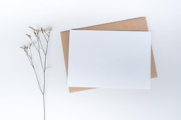 Carta bianca vuota su busta di carta marrone con fiore secco di limonium. vista dall'alto della busta di carta artigianale su sfondo bianco.