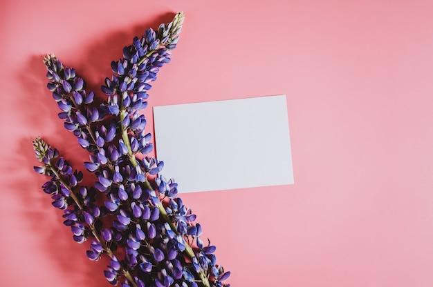 Mockup di nota carta carta bianca vuota per testo con cornice fatta di fiori lupino in colore blu lilla in piena fioritura su uno sfondo rosa piatto laici spazio per il testo Foto Premium
