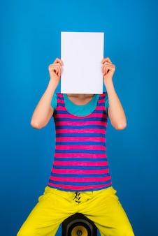 Carta bianca bianca sopra la testa ragazza che si copre il viso