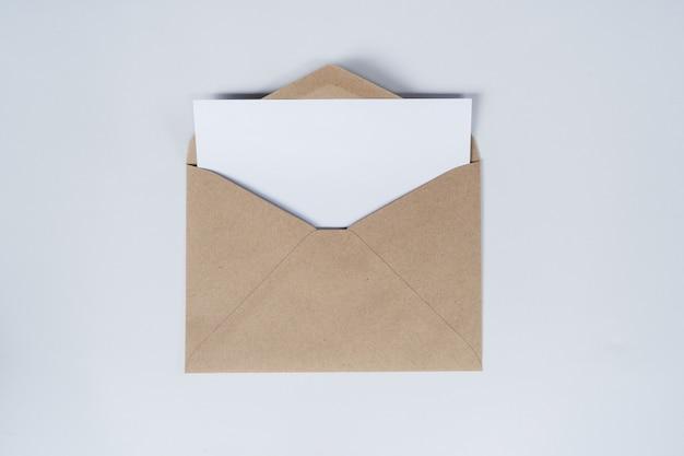 Il foglio bianco vuoto viene posizionato sulla busta di carta marrone aperta. vista dall'alto della busta di carta artigianale su sfondo bianco.