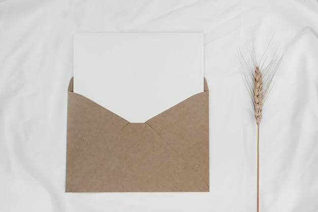 La carta bianca vuota viene posizionata sulla busta di carta marrone aperta con il fiore secco d'orzo su un panno bianco. vista dall'alto della busta di carta artigianale su sfondo bianco.