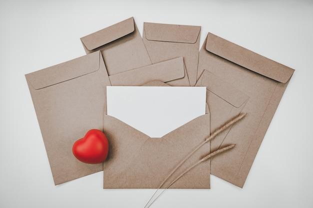 La carta bianca vuota è posta sulla busta di carta marrone aperta con cuore rosso e fiore secco di coda di volpe ispida