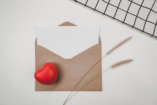 La carta bianca vuota è posta su una busta di carta marrone aperta con cuore rosso, fiore secco di coda di volpe ispida
