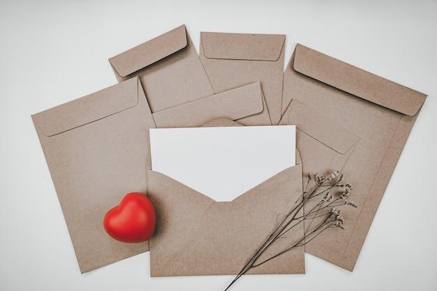 La carta bianca vuota è posta sulla busta di carta marrone aperta con cuore rosso e fiore secco di limonium