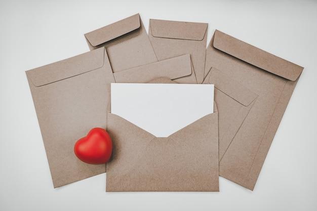 La carta bianca vuota viene posizionata sulla busta di carta marrone aperta con cuore rosso