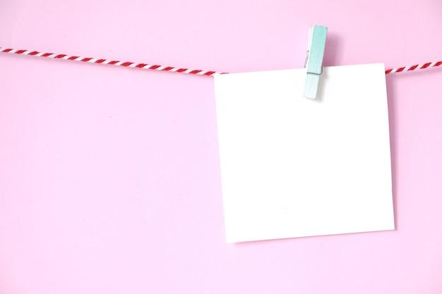 Blocco note in bianco del libro bianco che appende sul fondo rosa, con lo spazio della copia per testo