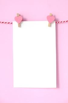 Blocco note in bianco del libro bianco che appende su fondo rosa