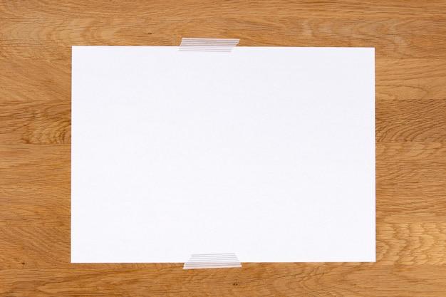 Bastone per appunti in carta bianca vuota su sfondo di legno con nastro adesivo grigio