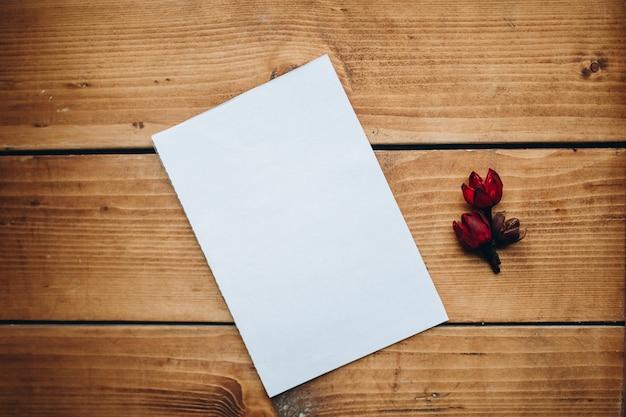 Libro bianco in bianco con fiore secco su una scrivania in legno.