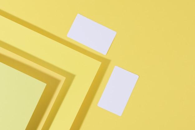 Biglietto da visita rettangolare bianco vuoto su sfondo giallo creativo da fogli di carta con ombra, vista dall'alto