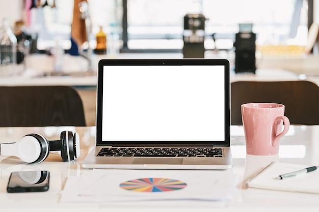 Schermo bianco vuoto del computer portatile con il telefono cellulare della tazza di caffè della cuffia e il documento del grafico di dati
