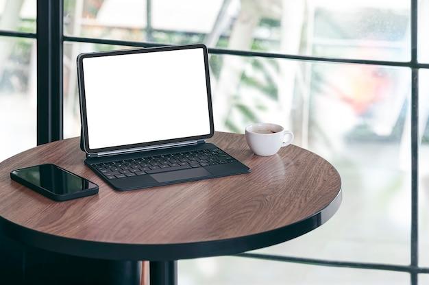 Tablet schermo bianco vuoto con tastiera magica e smartphone su tavola rotonda in legno nella sala bar.